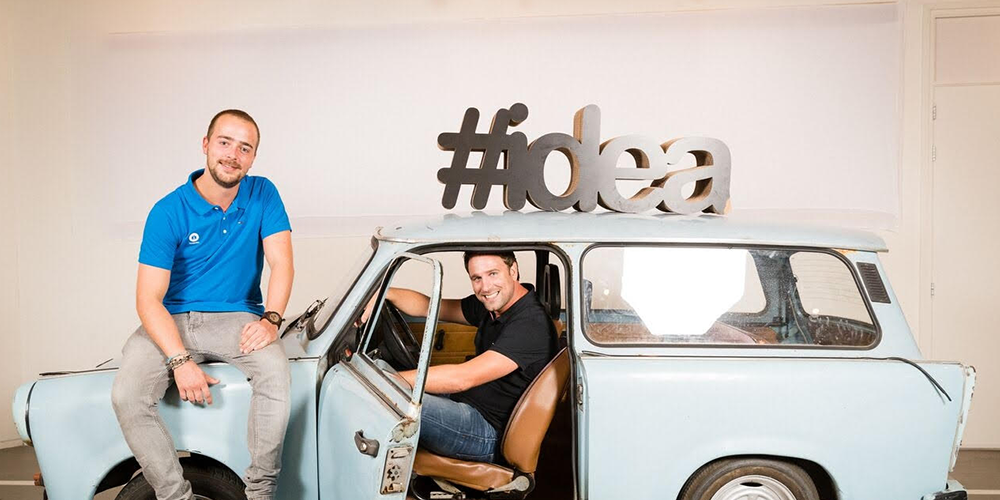 Two men sitting in and on top of a light blue vintage car