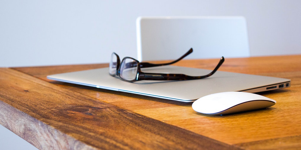 A laptop and glasses on a wooden table