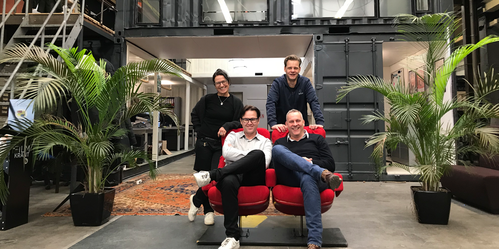Ticketing Group team sitting on red chairs in a coworking space