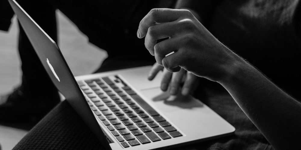 A black and white photo of someone's hands typing on a Mac laptop