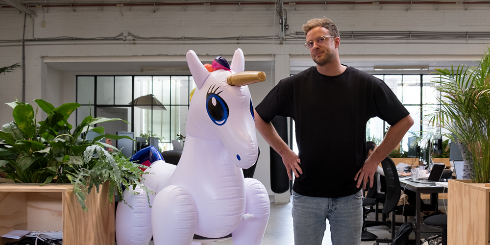 A man posing for a photo next to an inflatable unicorn
