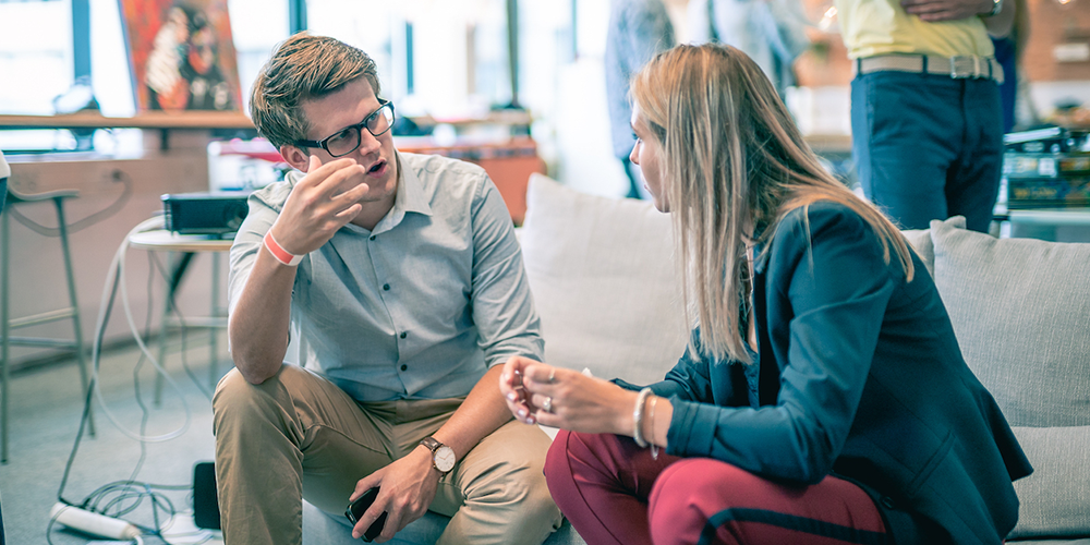 A man with glasses sitting and having a conversation with a woman