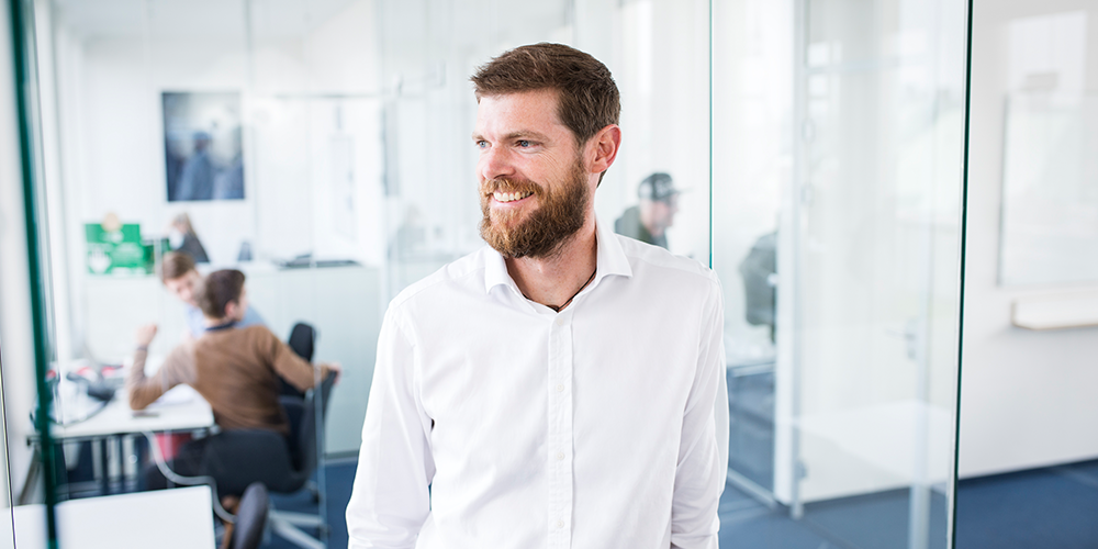 A man with a beard in a white shirt posing for a photo in the office