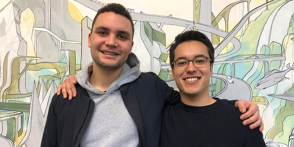 Two guys posing for a photo in front of a decorated wall