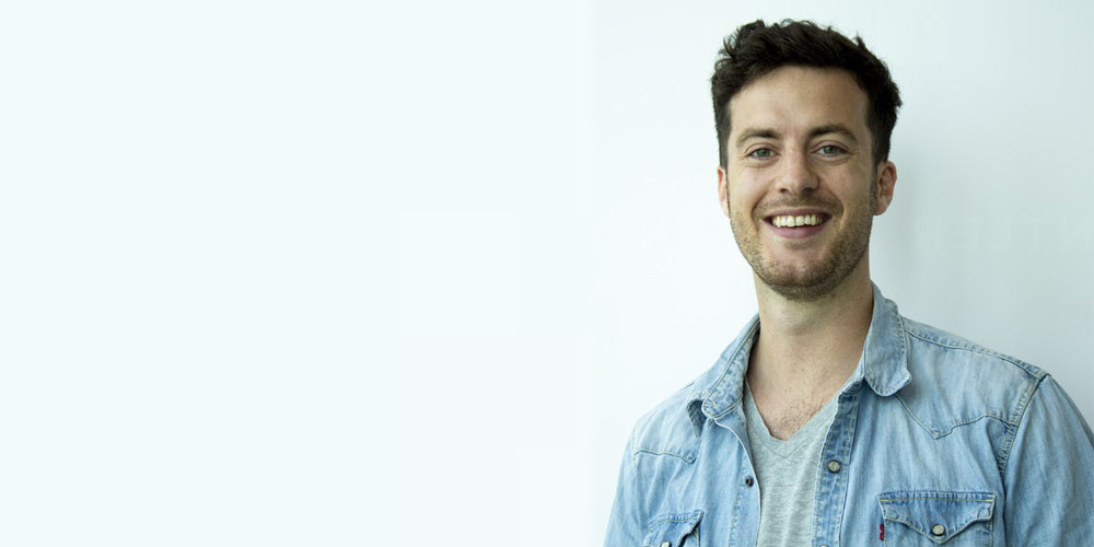 A guy with dark hair in a jean shirt posing for a photo