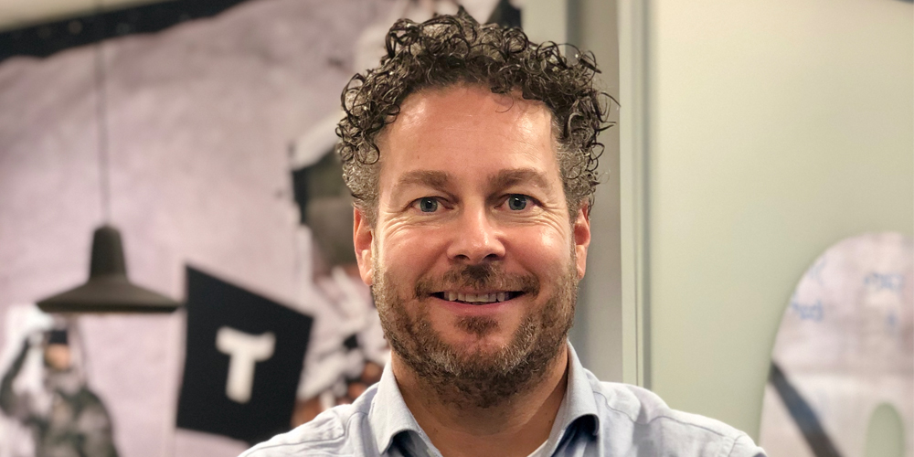 A man with curly hair posing for a photo