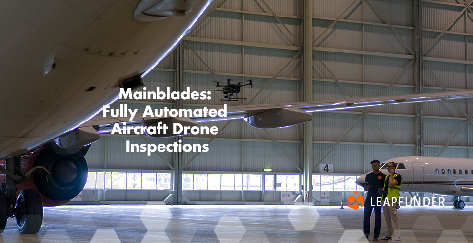A hangar with aeroplanes and two people inspecting them with a drone