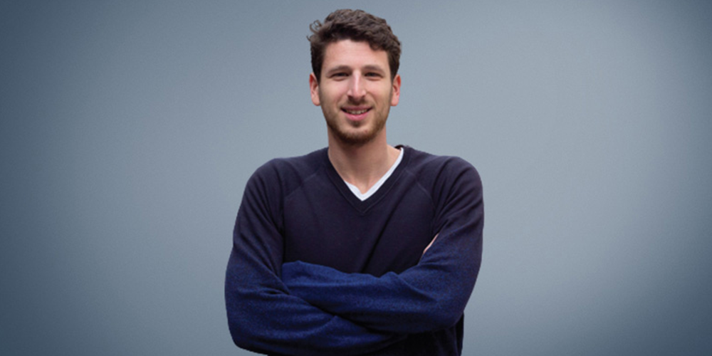 A man with brown hair, wearing a dark blue sweater, posing for a photo