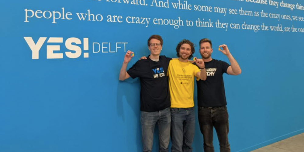 Three co-founders posing for a photo with their product